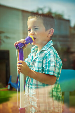Little cute boy singing into microphone at home photo