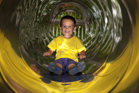 play boy: Happy child riding down slide on the playground
