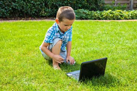 only one boy: Little boy using laptop outdoors