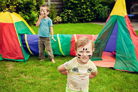 Children plaing with toy tent Stock Photo