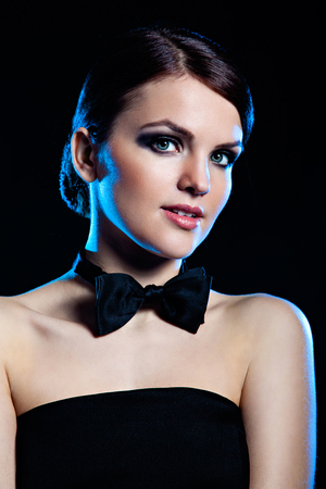 hair tie: Portrait of young beautiful girl wearing smoking bow-tie against black background
