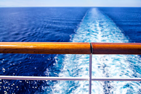 Cruise ship parapet and wake or trail on ocean surface Stock Photo