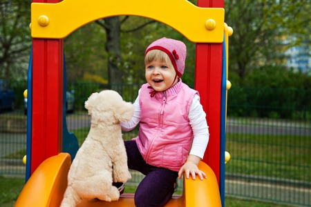 action girl: Little girl at playground with toy dog