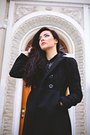 Woman near wood entrance door at street photo
