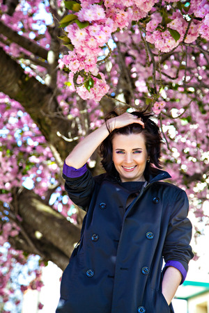 Young woman near tree blossom in park Stock Photo