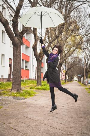 donna volante: Felice giovane donna volare con l'ombrello