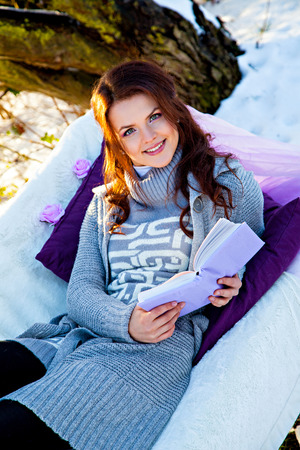Young woman sitting at sofa outdoors and reading book