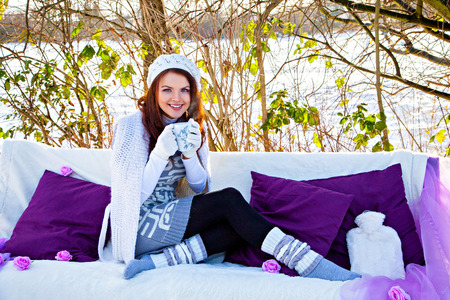 gets: Woman gets warm cup of tea in the winter forest