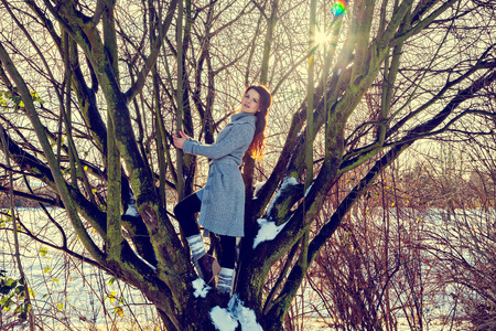 Woman at playful mood standing on tree Stock Photo