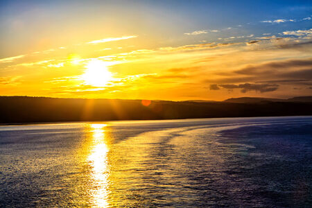 Golden sun is reflected on the surface of the sea photo
