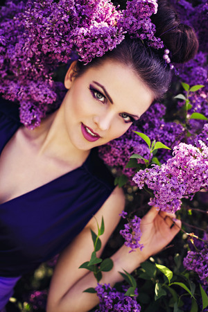 Beautiful girl in lilac ball dress among the flowers in the garden Stock Photo