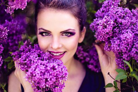 syringa: Beautiful girl in lilac ball dress among the flowers in the garden Stock Photo