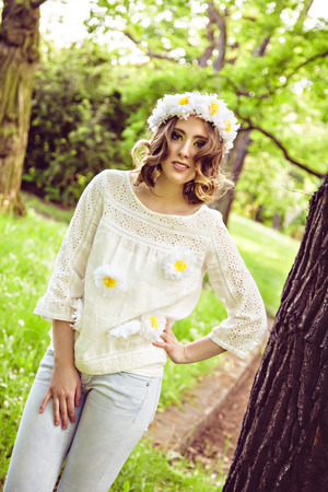 Young happy woman with daisy crown on head relaxing in a summer park photo