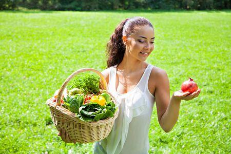 corbeille de fruits: Jeune fille avec un panier de fruits et l�gumes en plein air