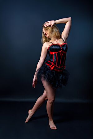 Burlesque dancer in short dress, black  background, on the stage photo