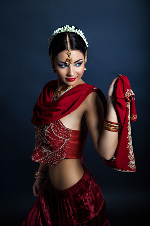 indian blue: Beautiful young woman in traditional indian clothing dancing