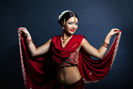 Beautiful young woman in traditional indian clothing dancing
