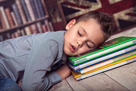 weary: Weary primary schoolboy fallen asleep on books