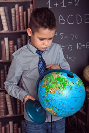 attentively: Primary schoolboy attentively studying globe
