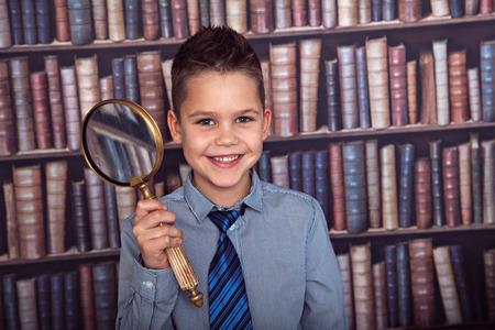ni�os estudiando: El muchacho sonriente, ni�o de primer grado con una lupa en la biblioteca