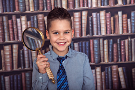 school age boy: Smiling boy, first-grader with a magnifying glass in library