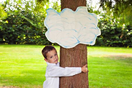 Little boy in white shirt clasped tree in park