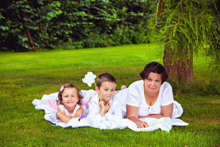 Grandmother and her grandchildren lying in the summer park Stock Photo