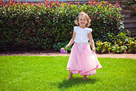 little colours: Happy girl in a pink skirt with hydrangea on the meadow in the garden
