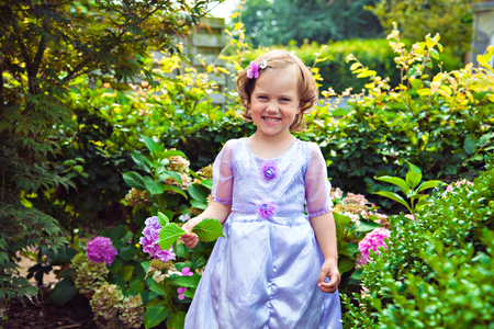 purple dress: Adorable girl in the purple dress with a flower hydrangea Stock Photo