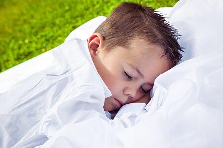 sweetly: Little boy sleeping sweetly in park