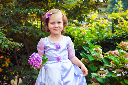 Adorable girl in the purple dress with a flower hydrangea Stock Photo