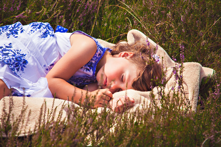 Small girl sweet dreaming in heather field Stock Photo
