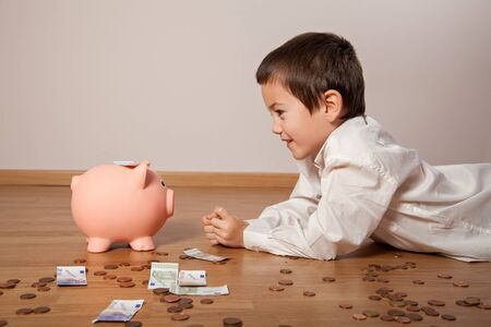 budget: Happy boy lying on the floor with money und a piggy bank