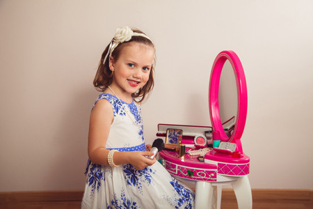 bead jewelry: Little girl making makeup on the beauty table Stock Photo