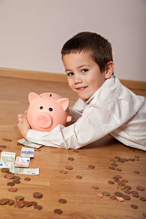family budget: Happy boy lying on the floor with money und a piggy bank