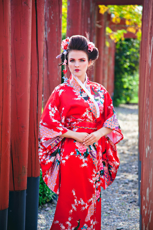 Young woman in geisha costume with fancy makeup in garden