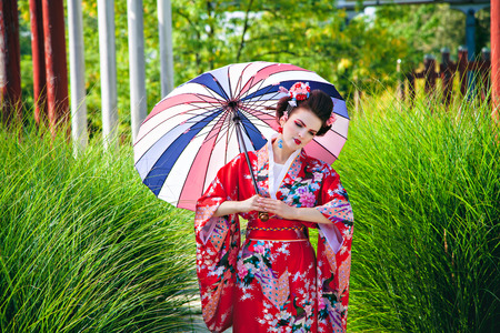 Girl in geisha costume with fancy make-up in the garden with an umbrella Stock Photo