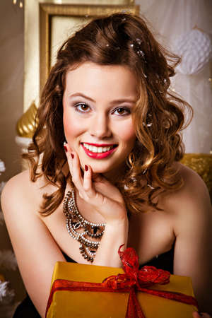 winter fashion: Joyful smiling young pretty woman with a necklace around her neck in evening dress with a Christmas gift