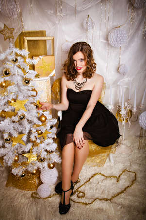 winter fashion: Beautiful young brunette woman in evening dress near Christmas tree