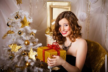 winter fashion: Beautiful young brunette woman in evening dress with a gift in her hands near Christmas tree