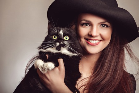hat nude: Beautiful young fashionable woman posing in black dress and black hat with cat in her hands. Vogue style. Studio photo