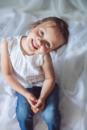 niños rubios: Niña sonriente linda con los ojos azules que se sientan en una cama Foto de archivo