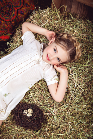 girl lying studio: Portrait of a girl in a white dress, lying on the hay near a nest with bird eggs. Studio photography in rustic style Stock Photo