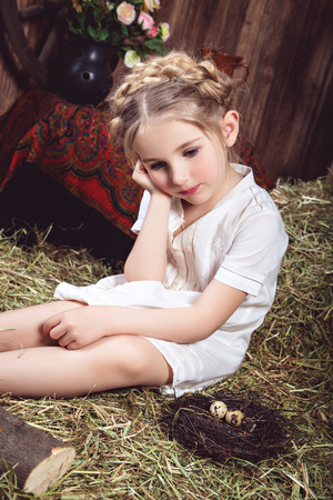 child girl: Portrait of a girl in a white dress, sitting on the hay near a nest with bird eggs. Studio photography in rustic style