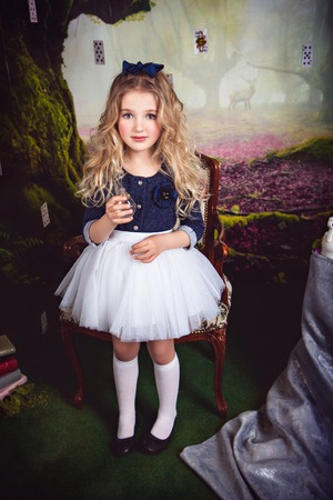 lewis carroll: Beautiful girl in the image of Alice in Wonderland with a glass bottle in her hand