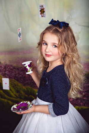 lewis carroll: Beautiful little girl in the image of Alice in Wonderland with a cup of tea in her hands