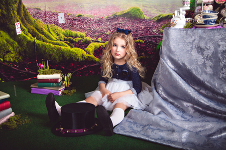 lewis carroll: Little sitting on the floor girl in a beautiful dress in the image of Alice in Wonderland and magician hat in front of her Stock Photo