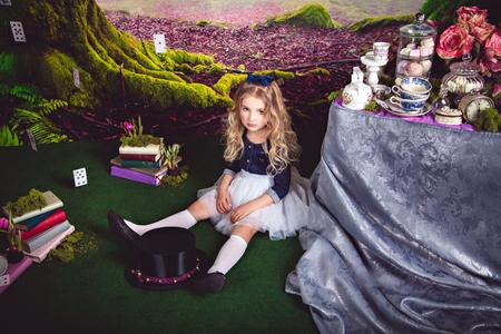 조금 바닥에 앉아 그녀의 앞에 이상한 나라의 앨리스와 마술사 모자의 이미지에 아름다운 드레스를 입은 소녀