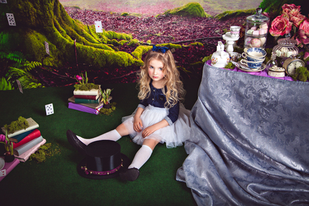 Little sitting on the floor girl in a beautiful dress in the image of Alice in Wonderland and magician hat in front of her Imagens