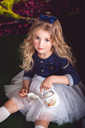 lewis carroll: Portrait of little sitting on the floor girl in a beautiful dress and blue bow in the image of Alice in Wonderland pouring tea Stock Photo